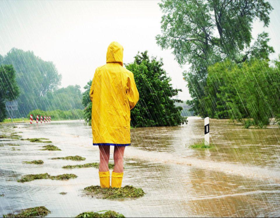 Frau steht im Regen auf Straße
